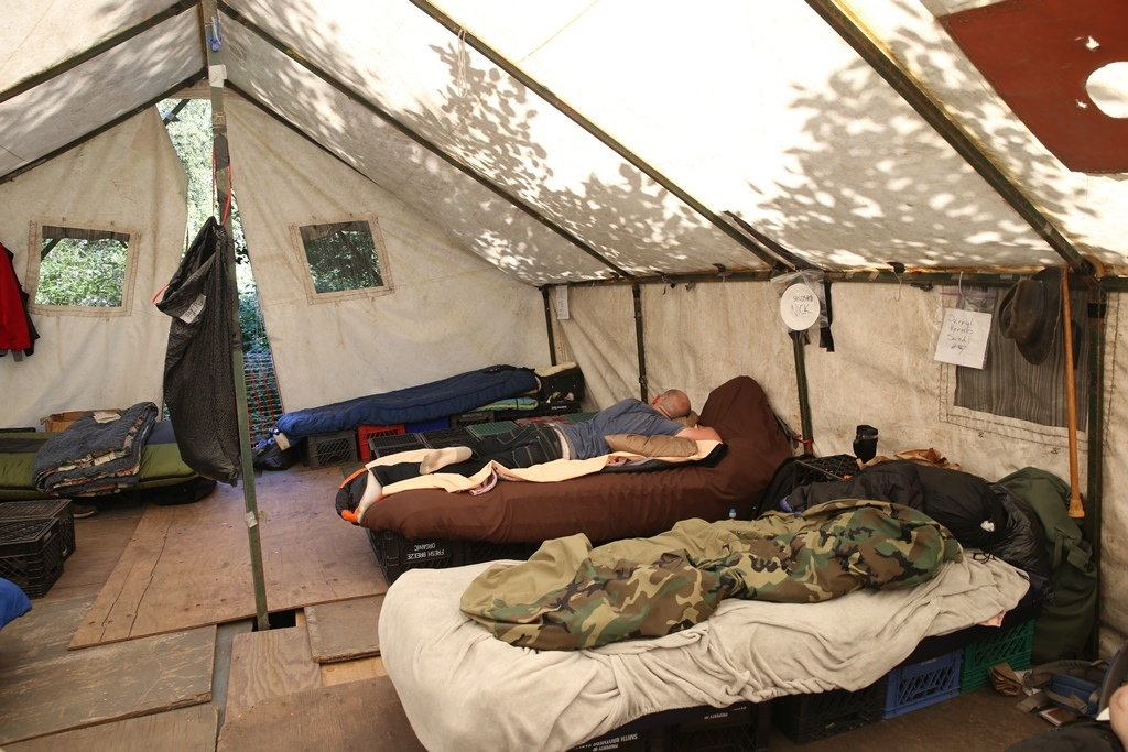 A resident of TC3 sleeps in shared tent