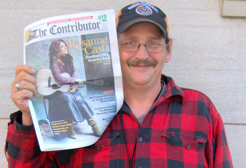 James E shows off the latest copy of The Contributor
