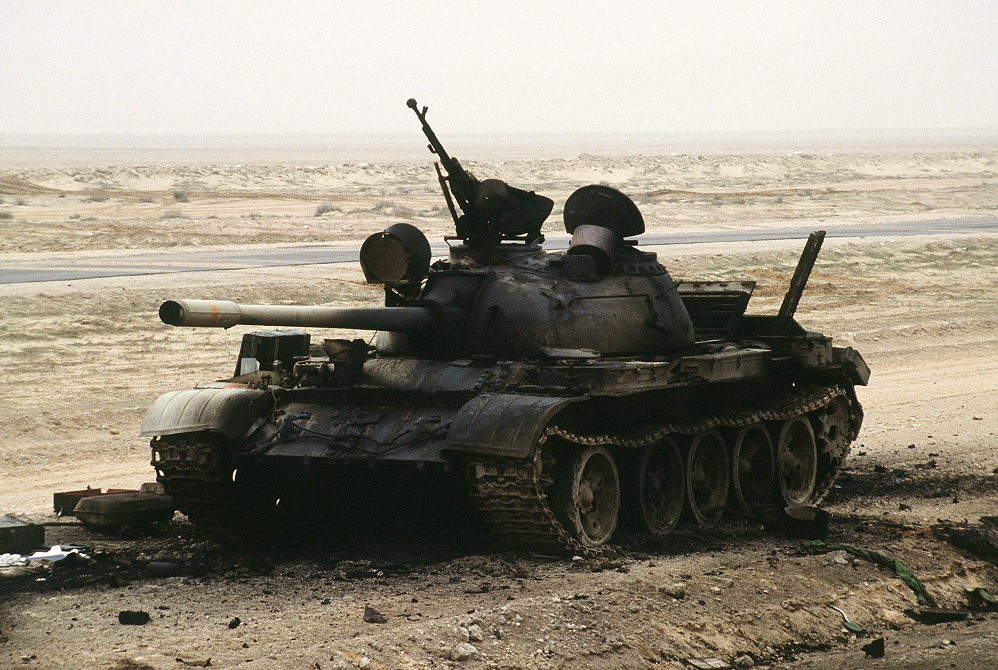 The charred remains of an Iraqi T-55 main battle tank sits on the Iraqi-Kuwait border, destroyed by Coalition armor heading into Kuwait during Operation Desert Storm. (Public domain)