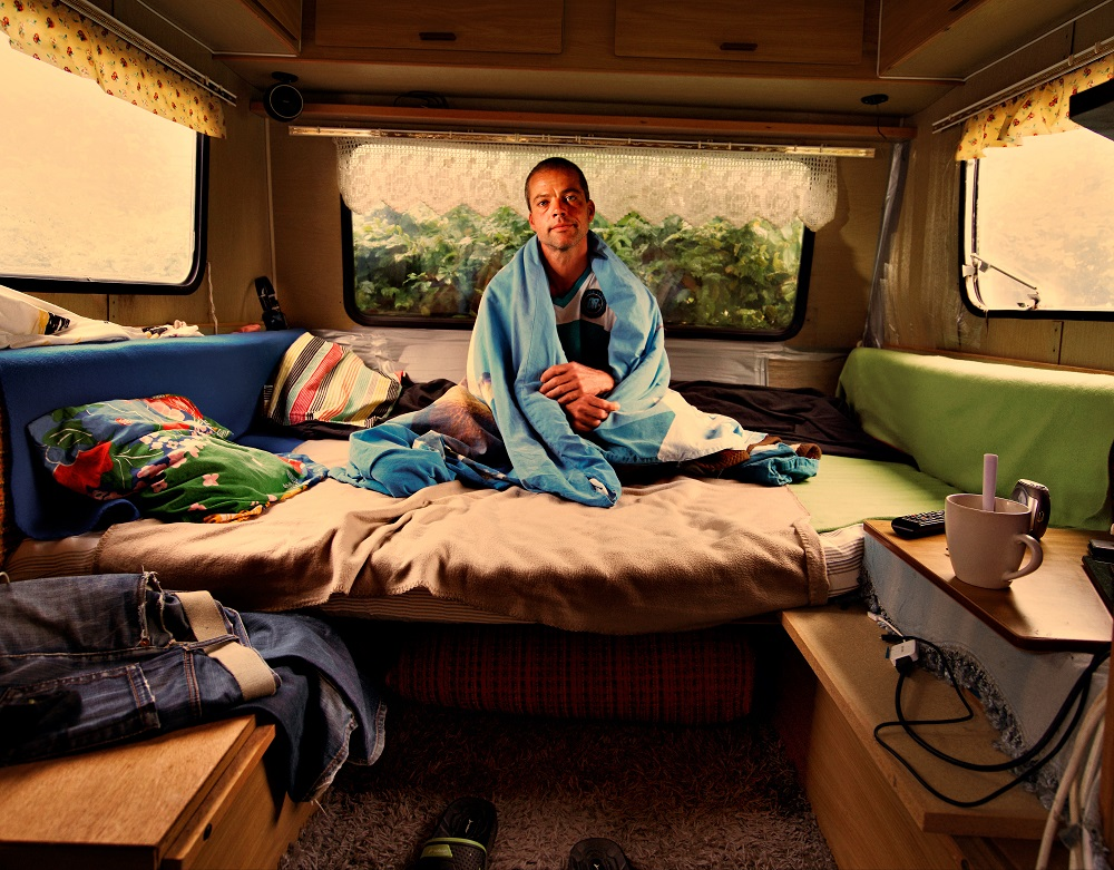 Csaba (January) from Hungary sits wrapped in a blanket inside the mobile home gifted to him by a Faktum customer. Credit: Håkan Ludwigson and Bo Kågerud