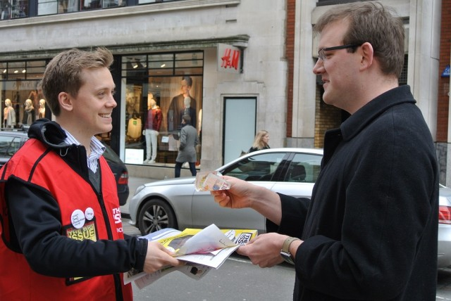 Owen Jones makes a sale. Photo: Laura Kelly<br>