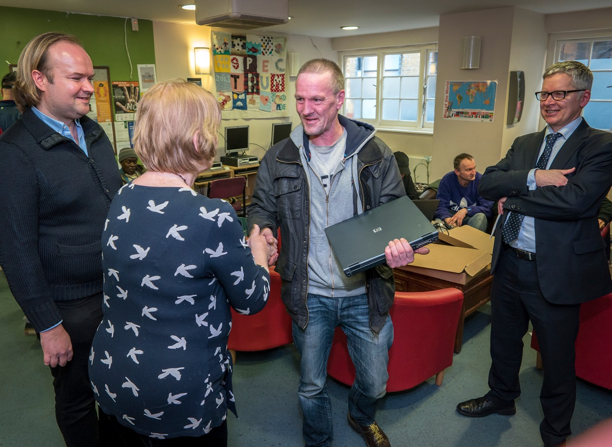 Thames Reach service user recerves laptop from Camden Councillor Patricia Callaghan, CEO of Thames Reach Jeremy Swain and Socialbox.biz founder Peter Paduh.
