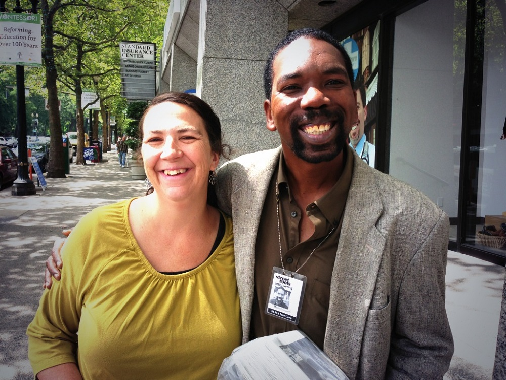 Street Roots vendor Marlon poses with a happy customer in Portland.