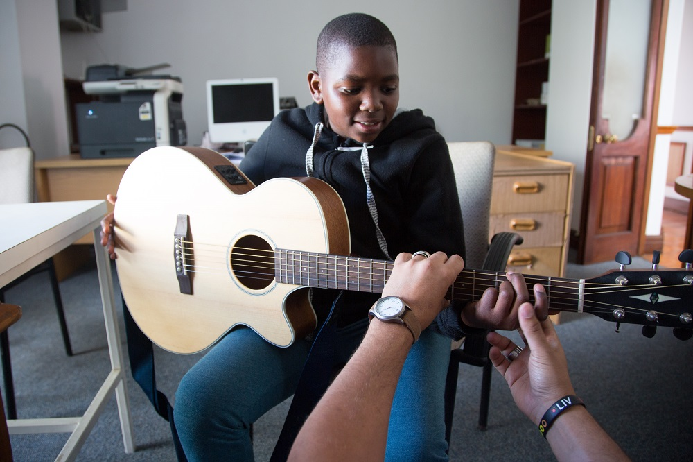 A volunteer musician with Guitars for Good teaches the child of a Big Issue South Africa vendor how to play guitar in Cape Town. Credit: Guitars for Good