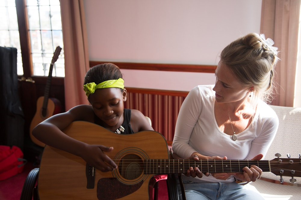 A volunteer musician with Guitars for Good teaches the child of Big Issue South Africa vendor how to play guitar during a free class held in the street paper's Cape Town office. Credit: Guitars for Good