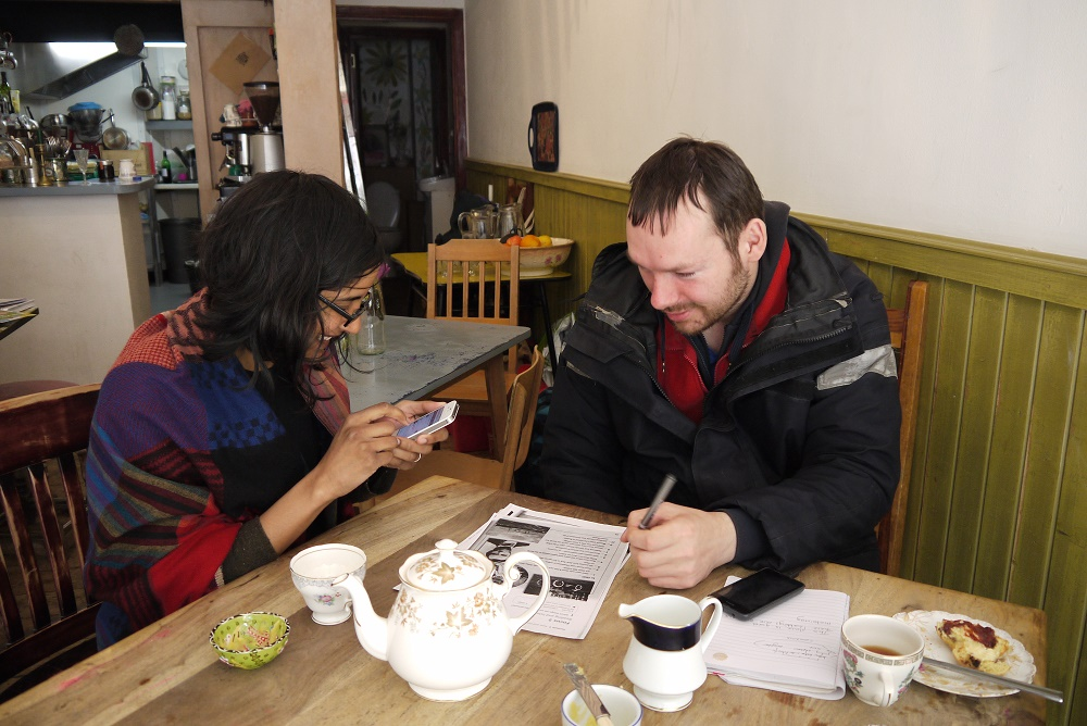 Dinushriya teaches Sebastian English using image cards, and translates on her phone. He describes what he sees in the past and present tense. The café creates a friendlyand warm environment to learn, they eat fresh scones with homemade lemon curd and jam.