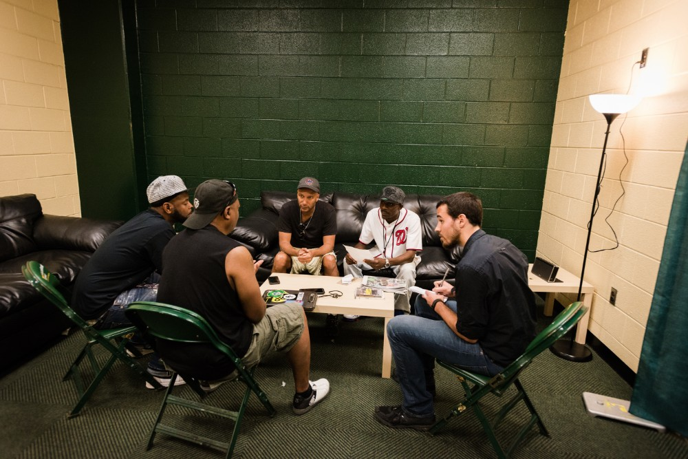 Street Sense editor-in-chief Eric Falquero (far right) with Ronald Dudley interviewing DJ Lord, Chuck D and Tom Morello from Prophets of Rage. Credit: Rodney Choice