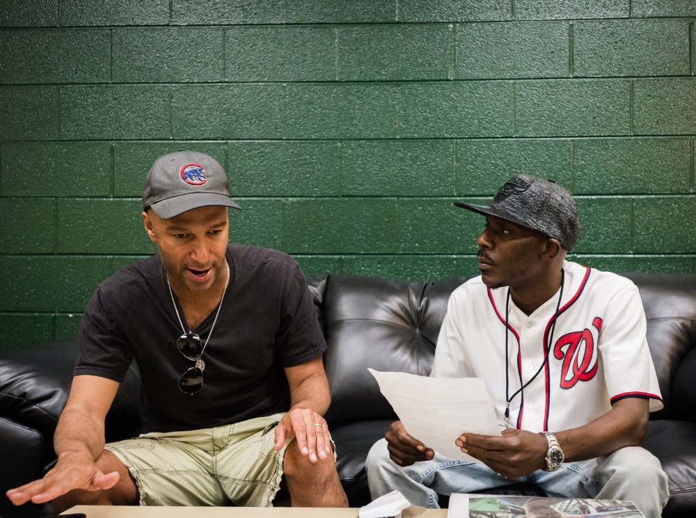 Tom Morello from Prophets of Rage chats to street vendor and rapper Ronald Dudley during their interview for Street Sense Credit: Rodney Choice