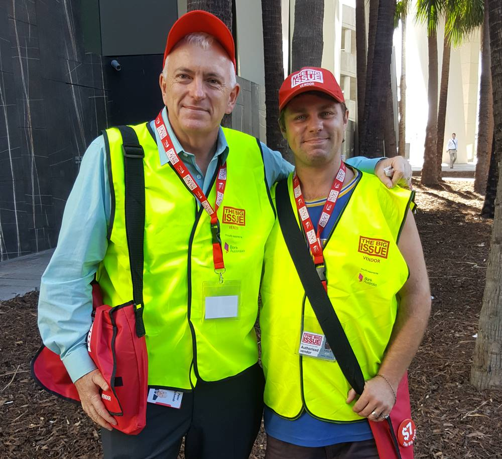 Peter Schmidt, partner at Norton Rose Fulbright, sells magazines with vendor Gary in Brisbane