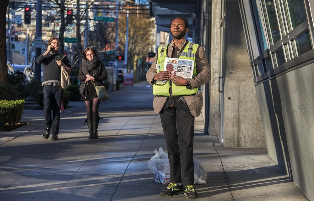 Real Change vendor William Ellington, 25, stands on a sidewalk near an entrance to the Lower Queen Anne QFC, selling papers in 40-degree weather. He keeps possessions in two plastic bags at his feet. He says he hasn't made much money yet selling the paper, but is making connections he hopes will help in the future. (Credit: Steve Ringman / The Seattle Times)