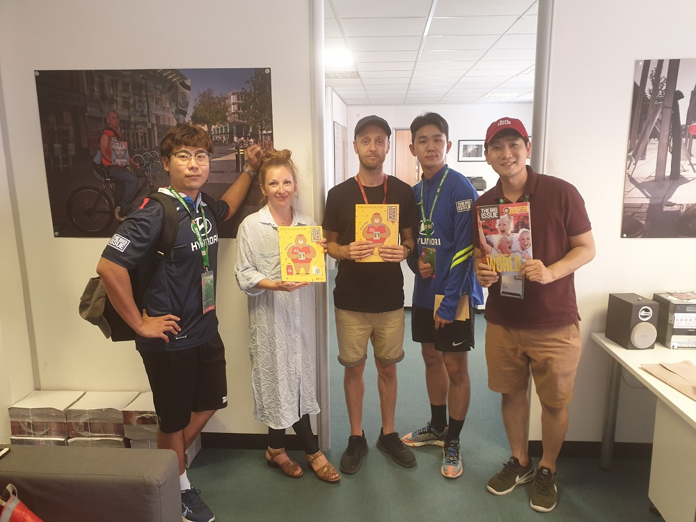 Big Issue (UK) staff based in the Cardiff office Lotty Talbutt and Tom Watts, flanked by representatives from The Big Issue Korea visiting while in the city for the 2019 Homeless World Cup.