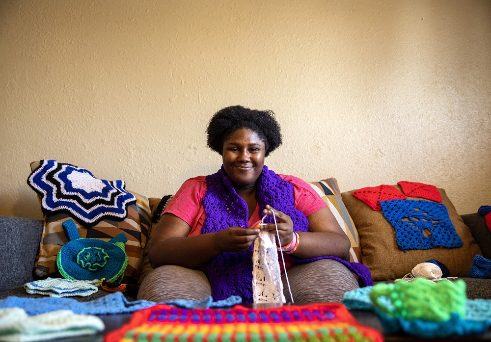 Precious sits with a collection of her yarn creations. She was in the beginning stages of working on a blanket when visited. [Credit: Nathan Poppe]