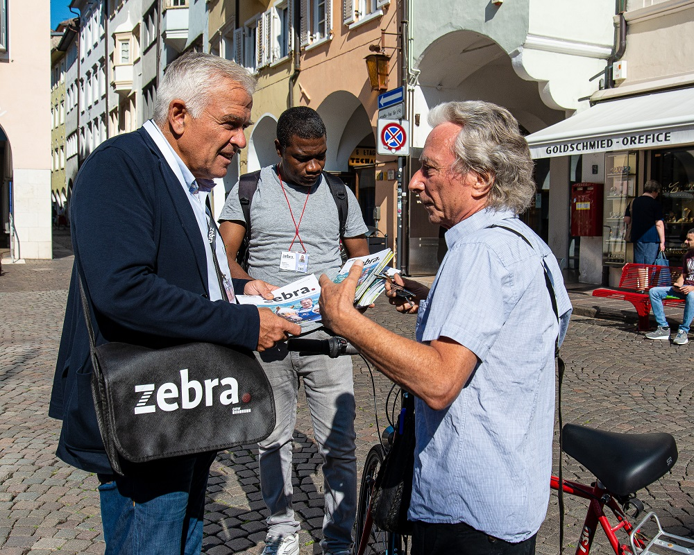 Heiner Oberrauch sells zebra. with vendor David. [Courtesy of zebra.]