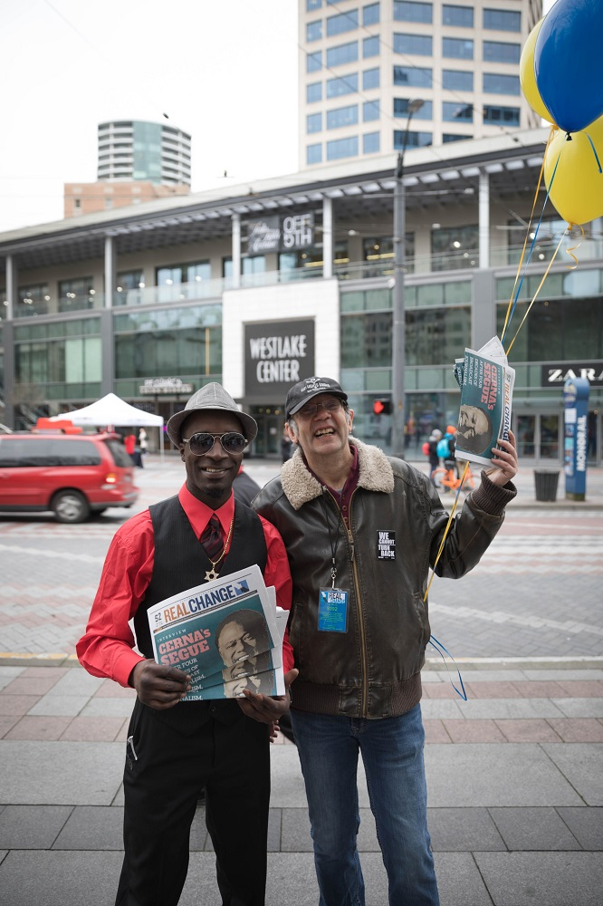Real Change Founding Director Tim Harris (right) sells copies of Real Change alongside vendor Darryl Manassa (left) for vendor week during Feb. 2018. [Photo by Sam Holman]