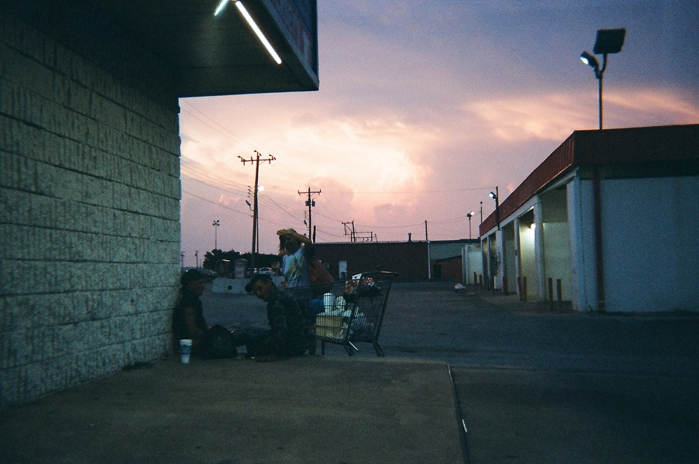 The sunset looms behind three people sitting outside the Ontrac Convenient Store in South OKC. Mark said he crouched to take the photo because he wanted to get a perspective from where his subjects were sitting.