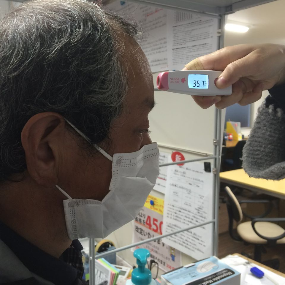 A Big Issue Japan vendor has their temperature taken. [Courtesy of The Big Issue Japan]