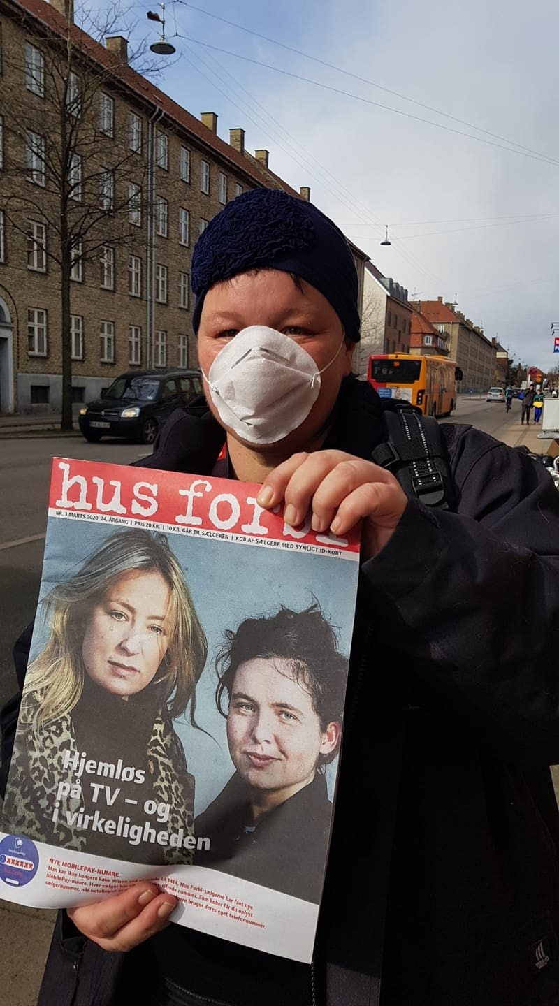 A Hus Forbi vendor sells the street paper while protecting herself with a face mask.