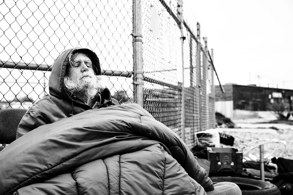 Jim kept warm under a sleeping bag on a freezing cold April 2 morning. He rarely leaves his camp and has been struggling with not being able to secure a bed at night. [Credit: Nathan Poppe]