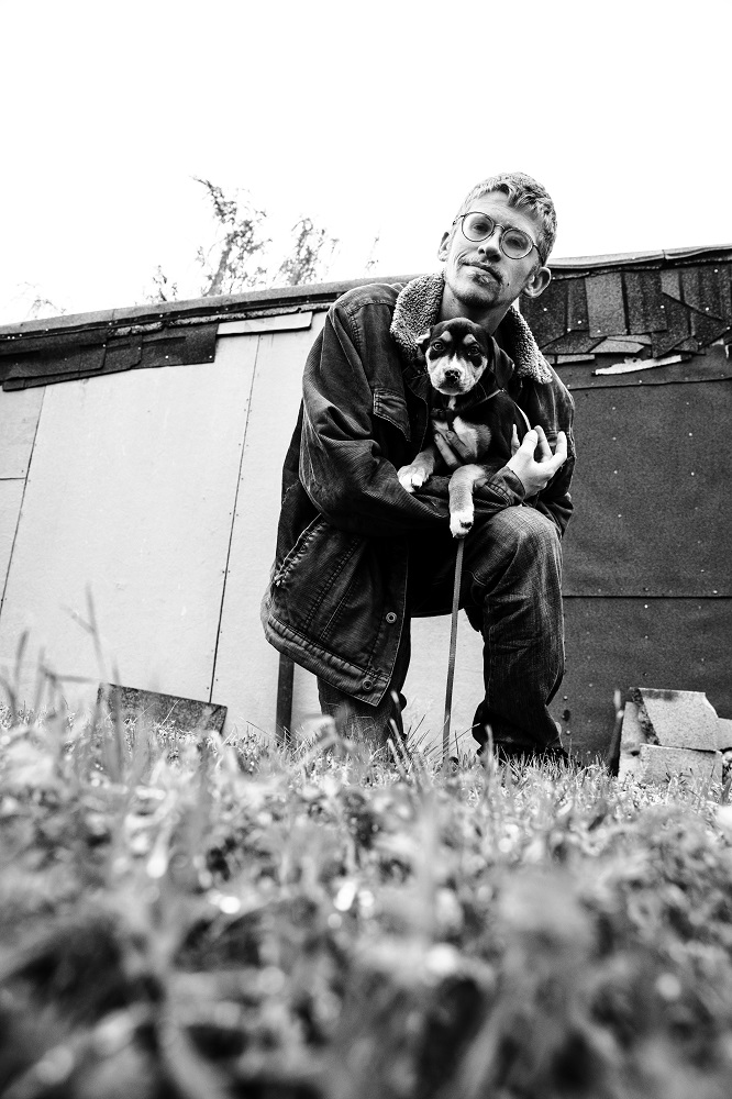 Colton holds his adopted dog, Pepper, which he started taking care of early in the pandemic. [Credit: Nathan Poppe]