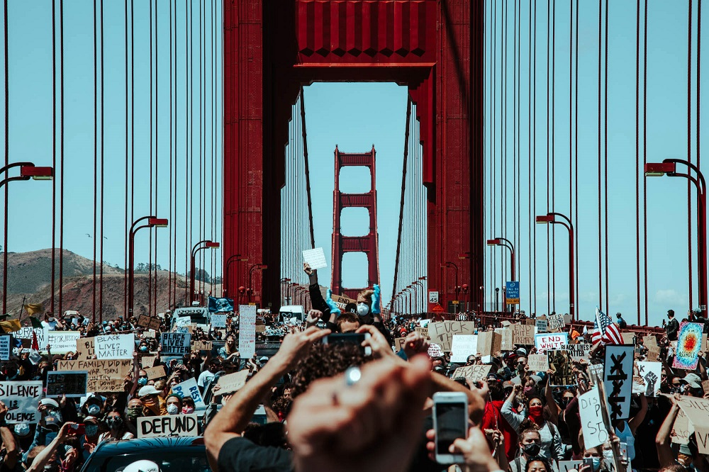 Having been confined to the pedestrian walkways for most of the march, protesters spill into the roadway and halt traffic on the Golden Gate Bridge. [Credit: Kit Castagne]