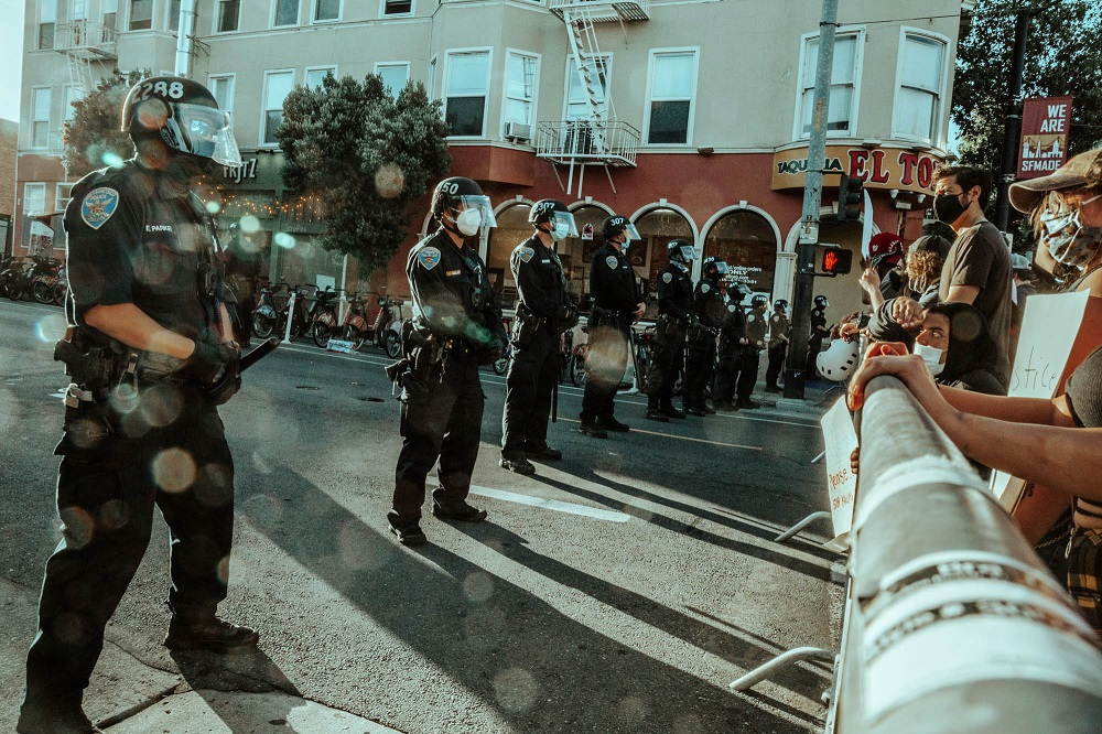 A line of police stand behind a barrier in front of protesters at the Mission police station. [Credit: Kit Castagne]