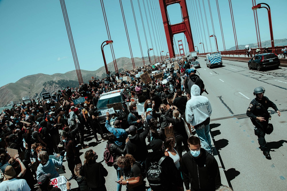A police officer rushes to communicate with fellow officers as an increasing number of protesters gather in the Golden Gate Bridge roadway. [Credit: Kit Castagne]