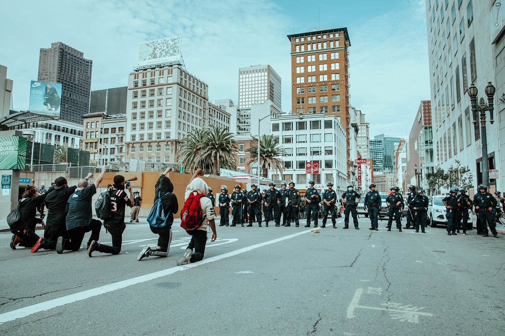 Protesters kneel in front of a line of police in Union Square. [Credit: Kit Castagne]