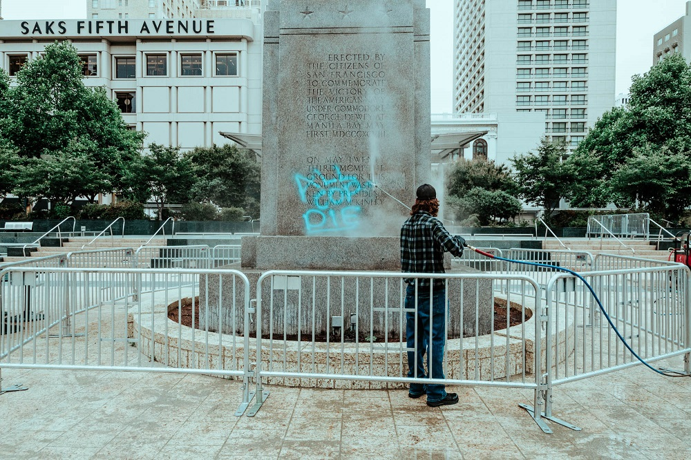 A man with a power washer removes anti-police graffiti from Union Square's Dewey Monument. [Credit: Kit Castagne]