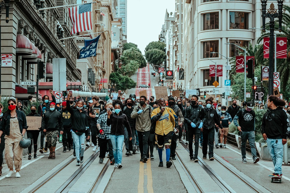 A group of protesters marches down Powell Street. [Credit: Kit Castagne]