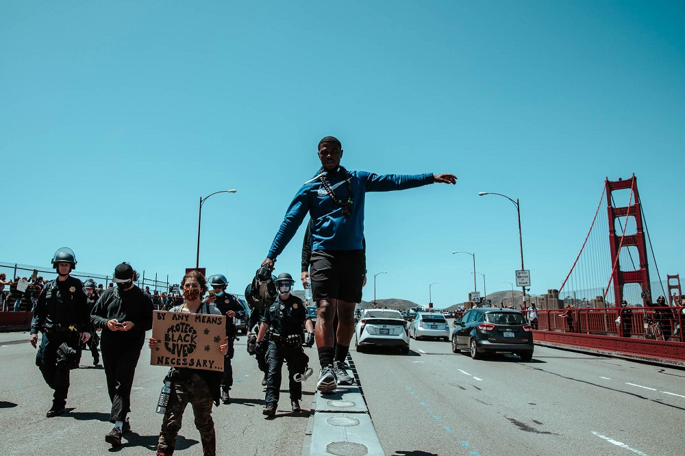 After news breaks that a woman in labor is stuck in the halted Golden Gate Bridge traffic, a protester with a megaphone asks marchers to unblock the road. [Credit: Kit Castagne]