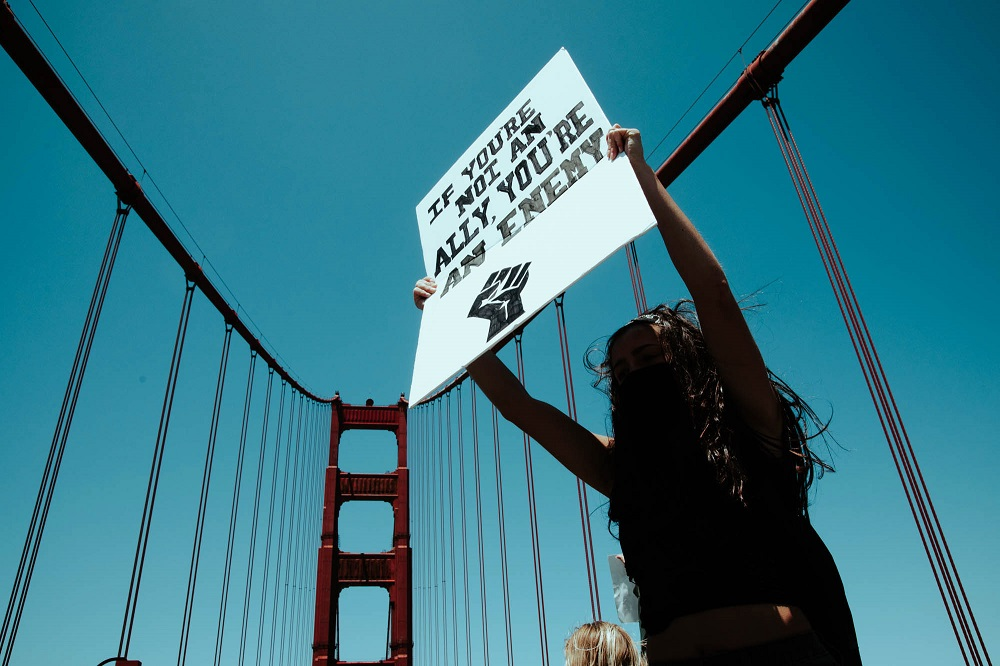A protester holds a sign while standing on the Golden Gate Bridge's median strip. [Credit: Kit Castagne]