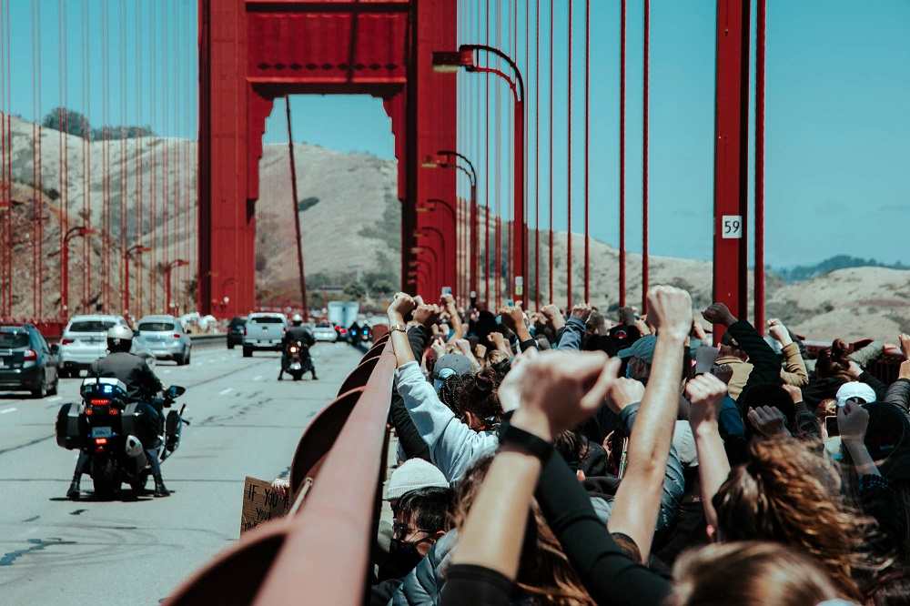 Protesters kneel together and raise their fists on the Golden Gate Bridge. [Credit: Kit Castagne]