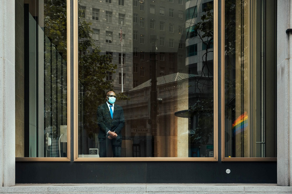 A man watches protesters march past from within an office building on Market Street. [Credit: Kit Castagne]