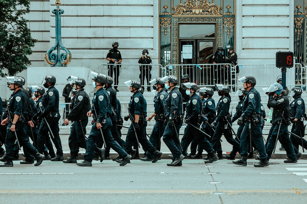 Police officers trail a protest marching away from City Hall. [Credit: Kit Castagne]