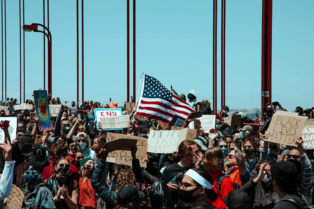 Protesters raise the American flag on the Golden Gate Bridge. [Credit: Kit Castagne]
