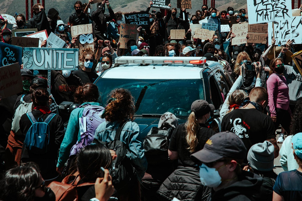 Protesters encircle a police car on the Golden Gate Bridge. [Credit: Kit Castagne]