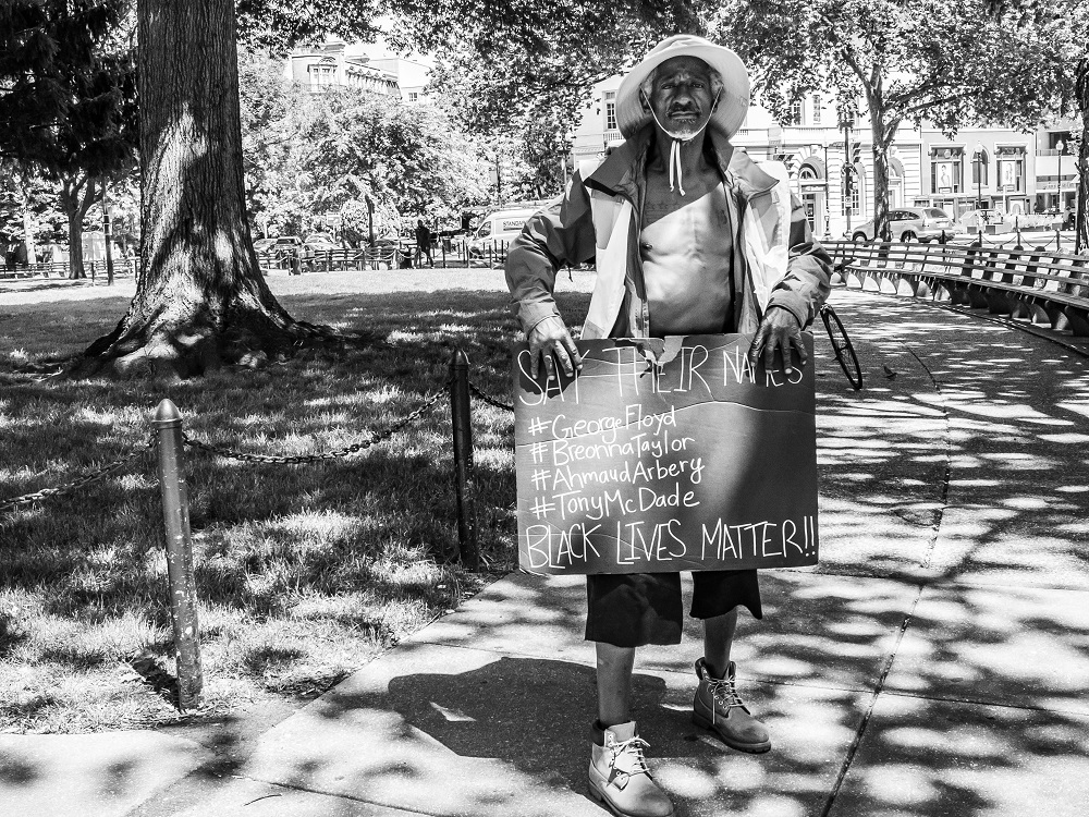 Moon - homeless in DC - with a sign for protest. [Credit: Benjamin Burgess / K Street Photography]