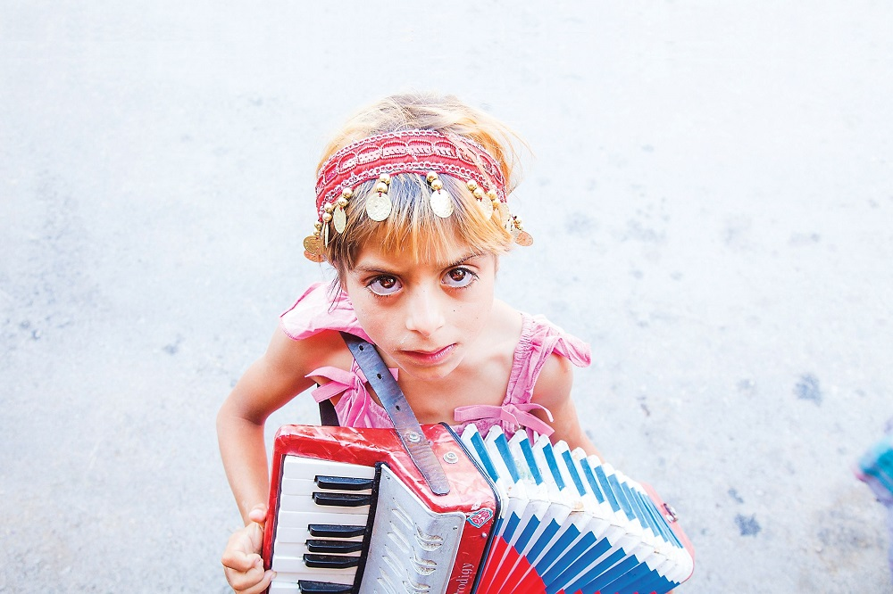 Romani girl playing the accordion in the street at the Guča Trumpet Festival in Serbia in 2014.