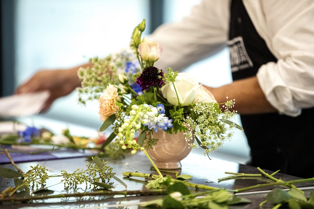 Gary works on a bouquet on the opening day of Curbside Flowers. [Credit: Nathan Poppe, The Curbside Chronicle]