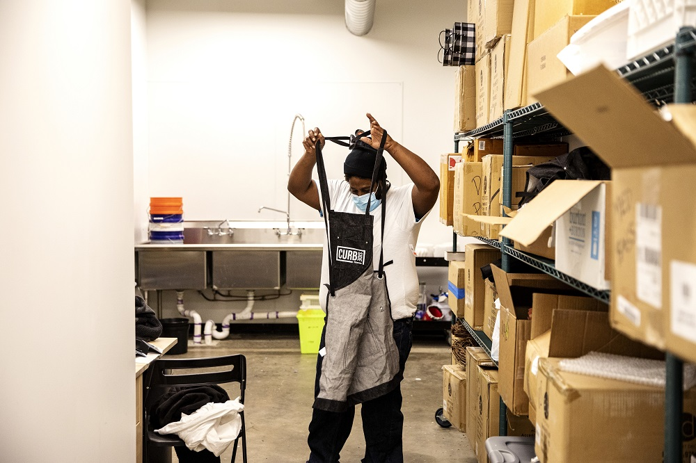 Corey ties his Curbside Flowers apron in the shop's backroom. [Credit: Nathan Poppe, The Curbside Chronicle]