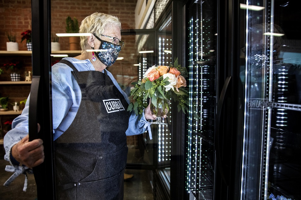 Marsha places a bouquet in the display fridge. [Credit: Nathan Poppe, The Curbside Chronicle]