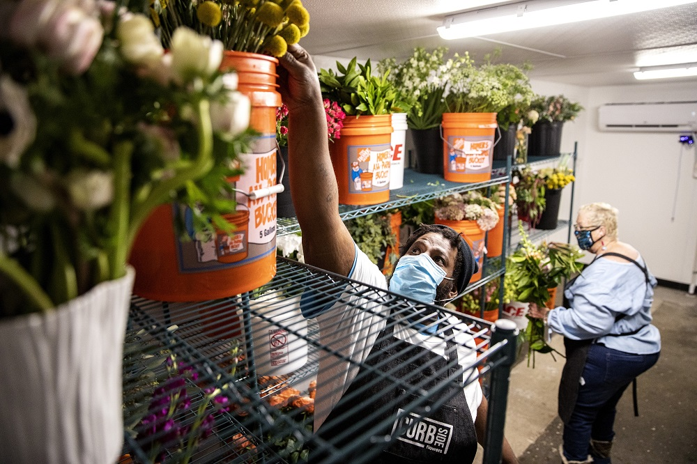 Corey reaches for a flower in the Curbside Flowers cooler. [Credit: Nathan Poppe, The Curbside Chronicle]