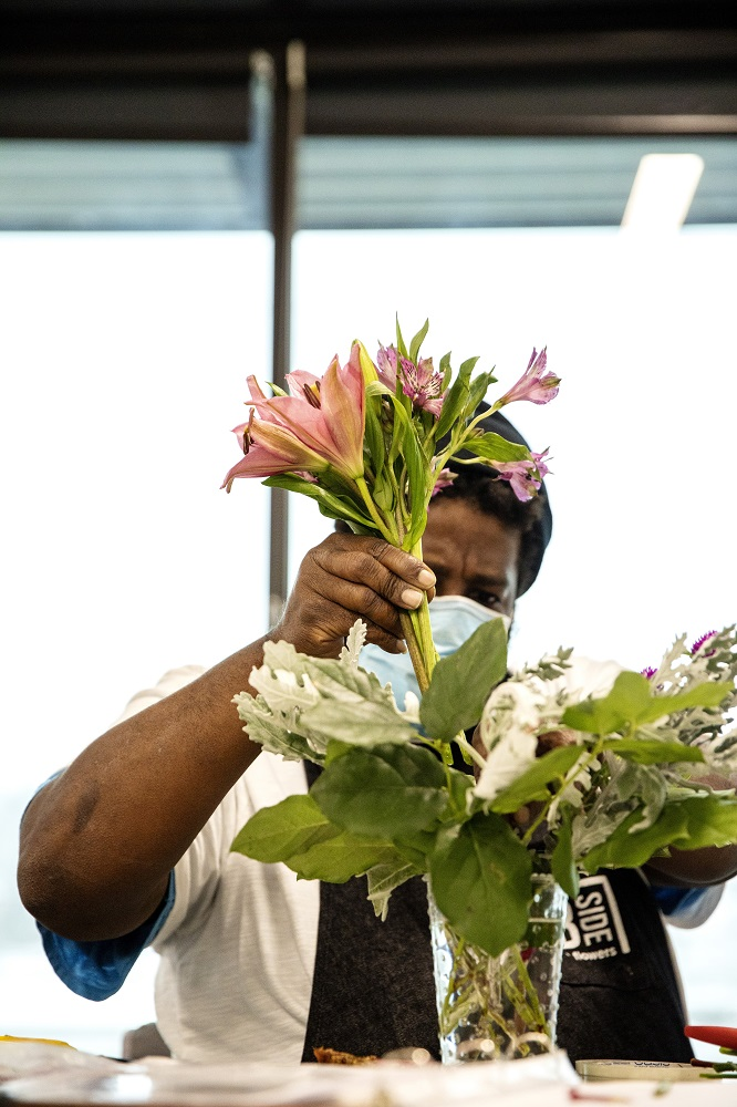 Corey working on a bouquet. [Credit: Nathan Poppe, The Curbside Chronicle]