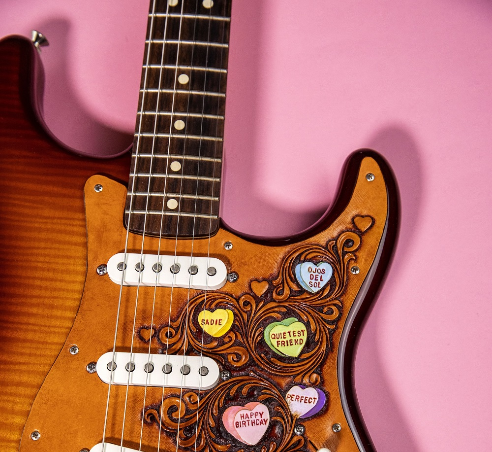 Oklahoma-based musician and artist Ali Harter created a custom leather guitar pickguard with song titles from the story in candy hearts. [Photo by Nathan Poppe, The Curbside Chronicle]